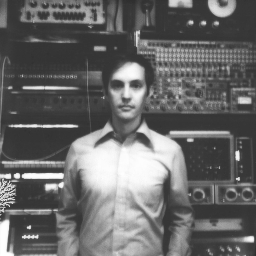 Black and white photo of Beau in front of a wall of recording equipment